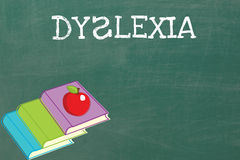 Dyslexia. The word Dyslexia  on a board, next to three books and an apple Stock Image