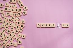Dyslexiekonzept - Alphabetbuchstaben auf rosa Hintergrund stockfotografie