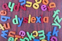 Dyslexitext med spridda alfabet på trätabellen Fotografering för Bildbyråer