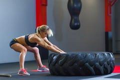 Dysponowana żeńska atleta pracująca z ogromną oponą out, ciągnie wewnątrz gym Crossfit kobieta ćwiczy z dużą oponą fotografia royalty free