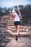 Dysponowana aktywna kobieta działająca w górę schodków w plenerowym krajobrazie obraz stock
