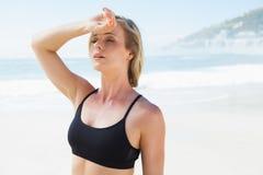 Dysponowana blondynka wyciera jej czoło na plaży Zdjęcie Stock