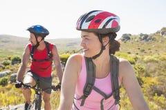 Dysponowana cyklista para ono uśmiecha się wpólnie na halnym śladzie Zdjęcia Royalty Free