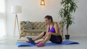 Dysponowana kobieta ogląda online wideo z ćwiczeniami na laptopie zbiory wideo
