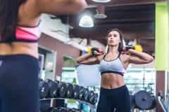 Dysponowana kobieta patrzeje lustro, ćwiczy z kettlebell w gym Zdjęcie Stock