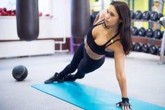 Dysponowana kobieta robi bocznemu deski joga pozy pojęciu fotografia stock