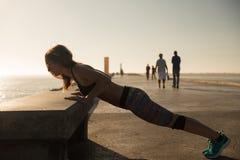 Dysponowana kobieta robi exercices na lato zmierzchu Fotografia Royalty Free