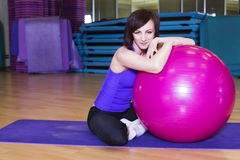 Dysponowana kobieta robi ćwiczeniom z piłką na macie w Gym Fotografia Stock