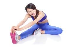 Dysponowana kobieta rozciąga jej nogę grzać up Fotografia Stock