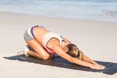 Dysponowana kobieta rozciąga ona na ćwiczenie macie z powrotem Zdjęcie Stock