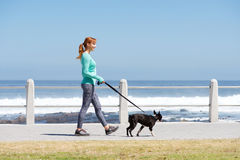 Dysponowana kobieta uśmiecha się psa na ścieżce i chodzi morzem Zdjęcie Royalty Free