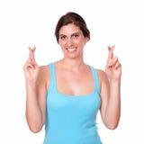 Dysponowana młoda kobieta krzyżuje ona palce zdjęcie stock