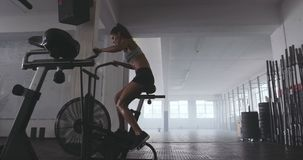 Dysponowana młoda kobieta używa ćwiczenie rower przy gym zbiory