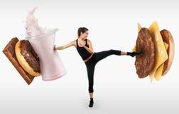 Dysponowana młoda kobieta walcząca z fasta food Zdjęcie Stock