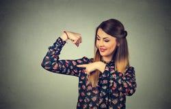 Dysponowana młoda zdrowa wzorcowa kobieta napina mięśnie pokazuje ona siłę obrazy stock