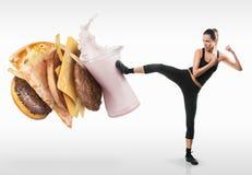 Dysponowana młoda kobieta walcząca z fasta food Fotografia Royalty Free