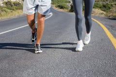 Dysponowana para biega wpólnie w górę drogi Zdjęcia Stock