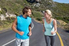 Dysponowana para biega wpólnie w górę drogi Obraz Royalty Free