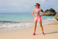 Dysponowana sportowa kobiety pozycja na plaży przygotowywającej dla treningu Obrazy Royalty Free