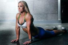 Dysponowana sprawności fizycznej kobieta robi niskiej rozciągliwości z powrotem Zdjęcia Royalty Free