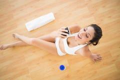 Dysponowana szczęśliwa kobieta wysyła tekst podczas jej treningu Zdjęcie Royalty Free
