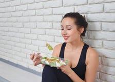 Dysponowana zdrowa kobieta je świeżej sałatki po sprawność fizyczna treningu w sportswear Fotografia Stock