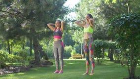Dysponowane kobiety rozciąga ramiona przed sprawności fizycznej szkoleniem zdjęcie wideo