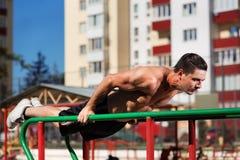 Dysponowane mężczyzna treningu ręki na upadów horyzontalnych barach trenuje triceps i bicepsy out podnoszą outdoors robić pcha Zdjęcie Stock