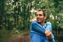 Dysponowane męskie jogger rozciągliwość podczas dnia szkolenia dla przecinającego kraju lasowego śladu ścigają się w natura parku zdjęcie royalty free