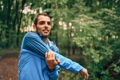 Dysponowane męskie jogger rozciągliwość podczas dnia szkolenia dla przecinającego kraju lasowego śladu ścigają się w natura parku obrazy stock