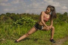Dysponowanego i sporty biegacza kobiety rozciągania Azjatycka noga i ciało po tym jak działający trening na zieleni pola pięknym  obrazy royalty free