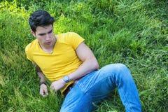Dysponowanego przystojnego młodego człowieka relaksujący lying on the beach na gazon trawie Fotografia Royalty Free