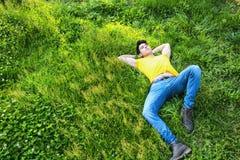 Dysponowanego przystojnego młodego człowieka relaksujący lying on the beach na gazonie Fotografia Royalty Free