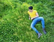 Dysponowanego przystojnego młodego człowieka relaksujący lying on the beach na gazonie Zdjęcie Stock