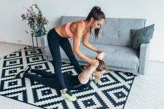 Dysponowanej kobiety pomaga przyjaciel w tylnym rozciąganie treningu w domu obrazy royalty free
