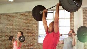 Dysponowani ludzie podnosi barbells w gym zbiory