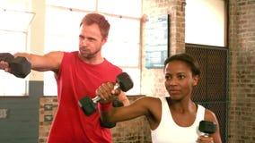 Dysponowani ludzie podnosi dumbbells w gym zbiory