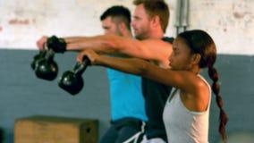 Dysponowani ludzie podnosi kettlebells w gym zdjęcie wideo