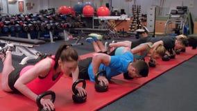 Dysponowani ludzie robić pchają podnoszą w gym zbiory