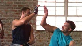 Dysponowani ludzie wysoki fiving w gym zbiory wideo