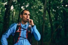 Dysponowani męscy jogger hydraty podczas gdy dnia szkolenie dla przecinającego kraju śladu lasowej rasy w natura parku fotografia stock