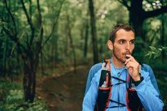 Dysponowani męscy jogger hydraty podczas gdy dnia szkolenie dla przecinającego kraju śladu lasowej rasy w natura parku fotografia royalty free