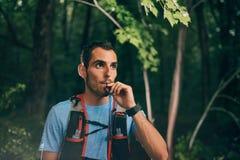 Dysponowani męscy jogger hydraty podczas gdy dnia szkolenie dla przecinającego kraju śladu lasowej rasy w natura parku zdjęcia stock
