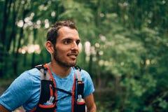 Dysponowani męscy jogger odpoczynki podczas dnia jogging dla przecinającego kraju lasowego śladu ścigają się w natura parku fotografia royalty free