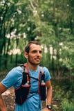 Dysponowani męscy jogger odpoczynki podczas dnia jogging dla przecinającego kraju lasowego śladu ścigają się w natura parku zdjęcia stock