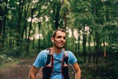 Dysponowani męscy jogger odpoczynki podczas dnia jogging dla przecinającego kraju lasowego śladu ścigają się w natura parku zdjęcie royalty free