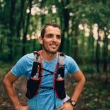 Dysponowani męscy jogger odpoczynki podczas dnia jogging dla przecinającego kraju lasowego śladu ścigają się w natura parku fotografia stock