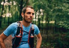 Dysponowani męscy jogger odpoczynki podczas dnia jogging dla przecinającego kraju lasowego śladu ścigają się w natura parku obrazy royalty free