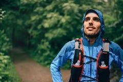 Dysponowani męscy jogger odpoczynki podczas dnia szkolenia dla przecinającego kraju lasowego śladu ścigają się w natura parku obrazy royalty free