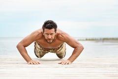 Dysponowany bez koszuli męski sprawność fizyczna model wewnątrz pcha up ćwiczenie Fotografia Stock